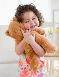 102561954-toddler-hugging-teddy-bear-smiling-gettyimages